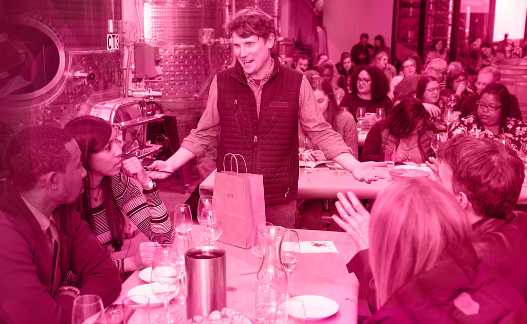 Man talking to group of diners with wine at a restaurant