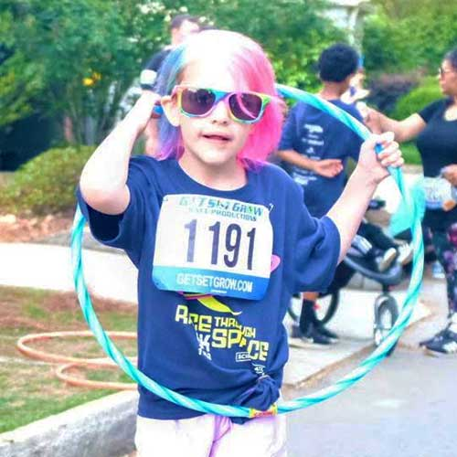 Young girl holding hula hoop at Race Through Space.