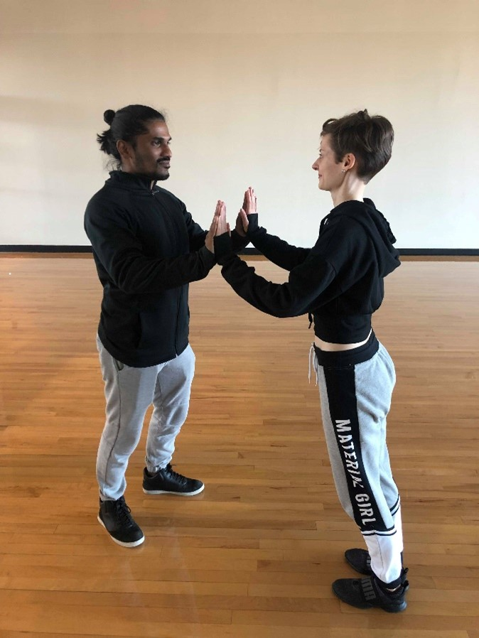 Ashwin and Kristen Anne stand facing each other with their palms pressed together.