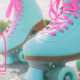 Close-up shot of a woman wearing colorful teal rollerskates with hot pink laces