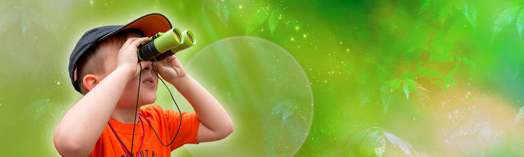 Young boy looking out with binoculars with a green abstract background