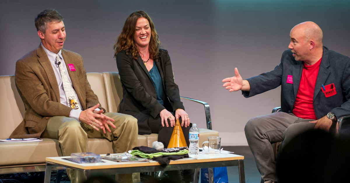 Three people laughing and having a conversation on stage